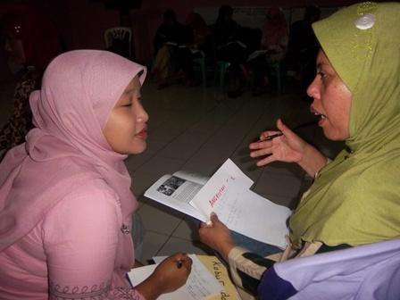 Ibu Lilis salah satu peserta pelatihan pengelolaan informasi buruh migran sedang melakukan praktik pewartaan