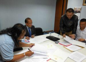 Fathulloh  (kiri) selaku kuasa dari BMI Hong Kong, Abdul Hamid Dipopramono(tengah), Ketua Komisi Informasi dan mediator sengketa, serta Tim KJRI Hong Kong (kanan) saat penandatangan kesepakatan mediasi sengketa informasi publik